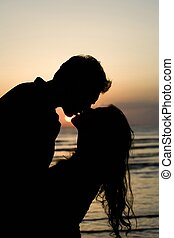 A silhouette of a couple about to kiss.