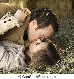 Young adult Caucasian couple lying down in hay kissing.