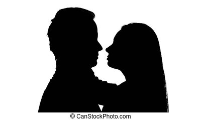 Kissing couple is standing in the studio, tender embraces turn into hot love. Silhouette. White background. Close up