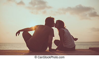 Kissing couple on the tropical sunset background