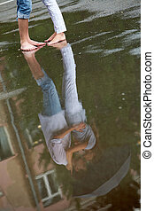 Kissing in the rain - Reflection in puddle of woman and man...