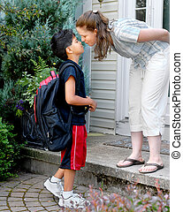 Kissing Mama Goodbye - Young elementary boy toting a...