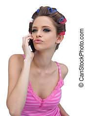 Kissing model wearing hair rollers with phone