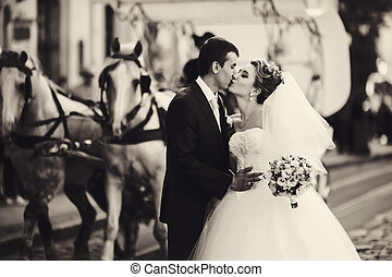 Kissing newlyweds stand in the front of a carriage with horses