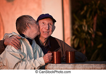 Kissing Senior Couple - Senior woman kisses happy man in hat...