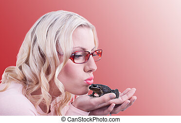 Kissing the frog - An attractive blonde woman is kissing a...