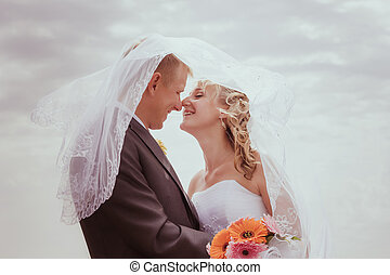 Kissing wedding couple in high grass