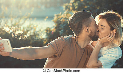Kissing young couple making selfie