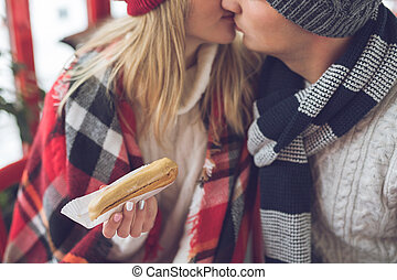 Kissing young couple with cake