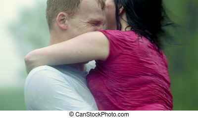 Kissing/playing in the rain - Young couple (man and woman),...