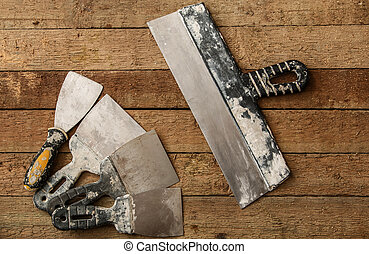 Kit of putty knives over wooden table