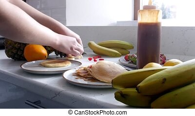 Kitchen - a woman lays bananas on pancakes and pours condensed milk