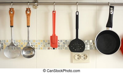 Kitchen accessories hang on hooks against a background of...