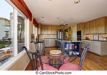 Kitchen and dining room interior with hardwood floor.