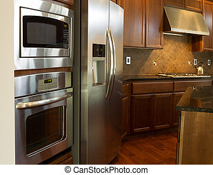 Closeup photo of a stainless steel appliances in modern residential kitchen with stone counter tops and cherry wood cabinets with hardwood floors