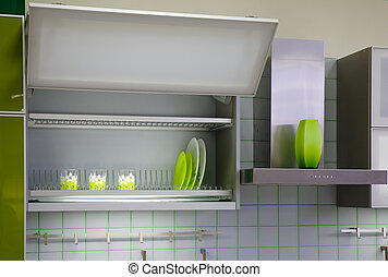 kitchen cabinet with green cups and dishes