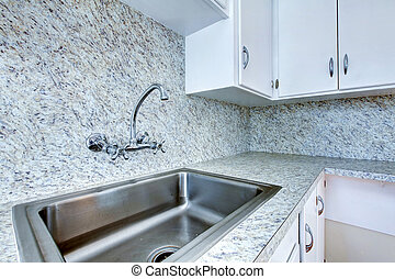 Kitchen cabinet with steel sink and granite counter top....