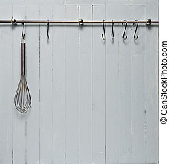 Kitchen cooking utensil on steel rack; steel whisk against rustic wooden wall; good copy-space