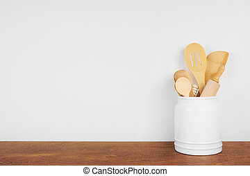 Kitchen cooking utensils on a wood shelf against a white ...