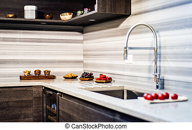 Kitchen corner with beautiful modern backsplash and cabinetry, colorfull fruits and vegetables around.