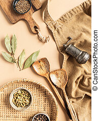Kitchen flat lay of beige apron, small bowls with spices, metal spice mill, wood kitchen utensils on beige background. Top view. copy space