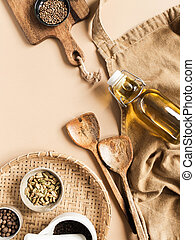 Kitchen flat lay of beige apron, small bowls with spices, olive oil in bottle, wood kitchen utensils on beige background. Top view. copy space