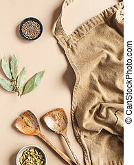 Kitchen flat lay of beige apron, small bowls with spices, wood kitchen utensils on a beige background. Top view. copy space