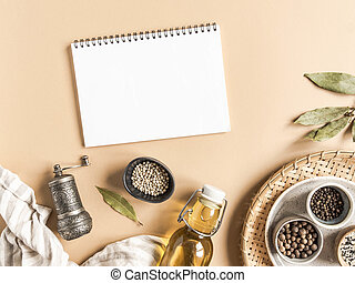 Kitchen flat lay with open notebook for culinary text and small bowls various dry spices and olive oil in glass bottle on beige background. Top view. copy space