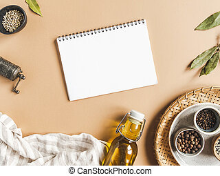 Kitchen flat lay with open notebook for culinary text and small bowls various dry spices and olive oil in glass bottle on a beige background.