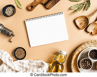 Kitchen flat lay with open notebook for culinary text and small bowls various dry spices, wood kitchen utensils, olive oil in glass bottle on beige background. Top view. copy space