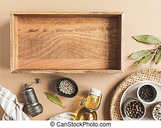 Kitchen flat lay with wood tray for culinary text and small bowls various dry spices and olive oil in glass bottle on beige background. Top view. copy space