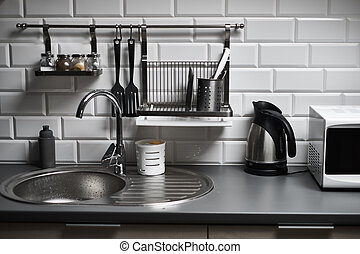 Kitchen in a loft style with concrete and brick walls and tiles, a sink, microwave, teapot and a modern lamp.