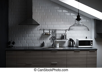 Kitchen in a loft style with concrete and brick walls and tiles, a sink, vent, microwave, teapot and a modern lamp.