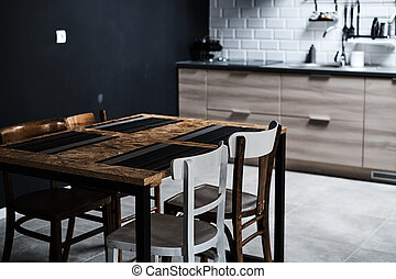 Kitchen in a loft style with concrete and brick walls and tiles. There is a black kitchen table with white chairs.