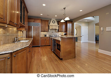 Kitchen in remodeled home with wood cabinetry