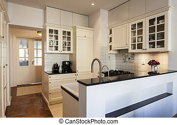 Kitchen with creamy shelves and white walls