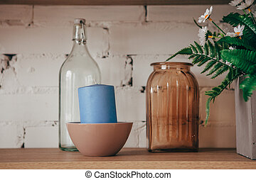 Kitchen interior: bottle, jar, candle and flowers in a vase on the shelf. Cozy home interior.