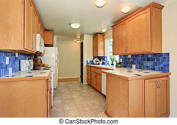 Kitchen interior. Maple cabinets and back splash trim.