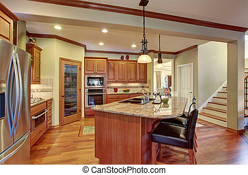 Kitchen interior with island. Wooden cabinets with granite counter top