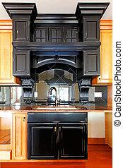 Kitchen island and stove custom wood cabinets. New luxury home interior.