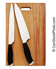 kitchen knives - two sharp kitchen knives on the breadboard