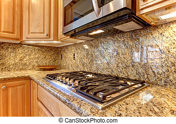 Kitchen microwave and stove top with granite background -...