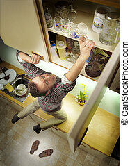 kitchen nightmare. man tries to climb a high cupboard to get a glass