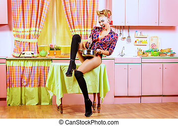 kitchen pin-up - Attractive pin-up girl cooking on her pink...