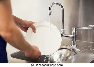 Kitchen porter cleaning white plates in sink in professional...
