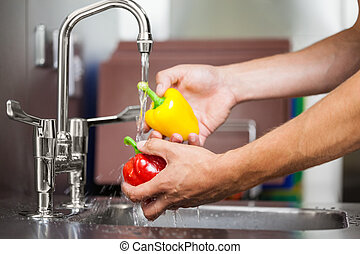 Kitchen porter washing pepper under running tap
