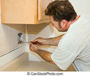 Electrician installing switch and receptacle in a kitchen during remodeling project.