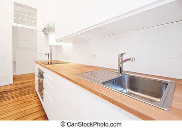 kitchen sink and water tap in new white kitchenette with wooden worktop