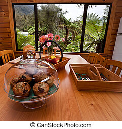 Kitchen table with muffins, fruit, bread and cutlery.