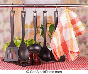 Kitchen tableware on hooks over kitchen background